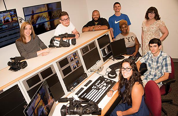 Staff members of MCN 87 pose for a picture in the station's control room in McCauley-Walsh Hall.