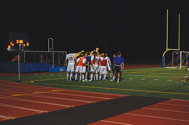 The soccer team huddles before they return to the game after halftime.