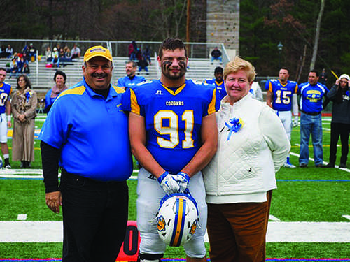 Senior defensive end Greg Zotian walks down the center of the field with his parents.