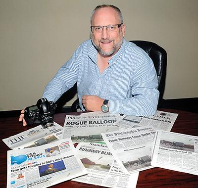 Jimmy May, adjunct professor in the communications department, took the defining photograph of the recent runaway Army balloon as it moved through Columbia County. Here he is seen with some of the newspapers that used his photograph.