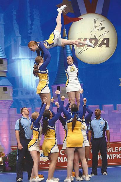 Members of the National Championship team complete a routine on the big stage as a judge looks on.