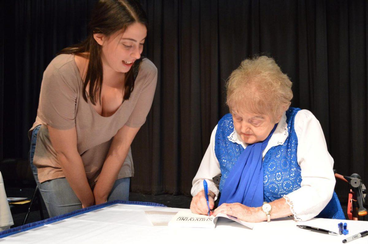 Sophomore speech-language pathology major Jacqueline Marchese watch Holocaust survivor, Eva Mozes Kor, sign a copy of her book: