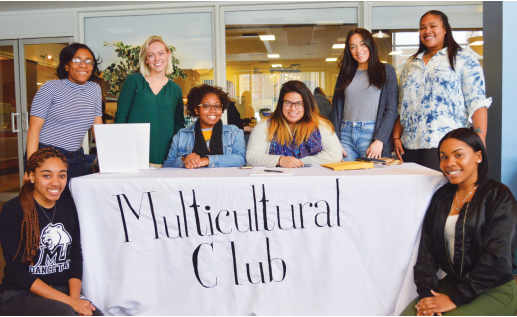 Left to right: Multicultural Club members Gardyney Deshommes, Noni Silas, Kierra Kimble, Habrienne Louchie, Chabely Espinal, Gabrielle Padilla, Tayler Fleming, and Creily Torres pose by their club's sign-up and information table.