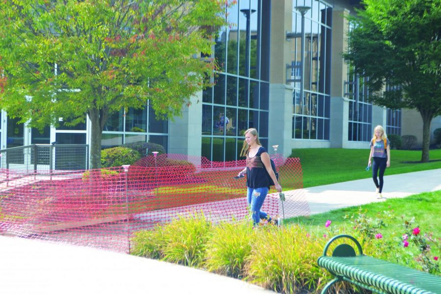 Students walk around the sidewalk construction. The construction started during the first two weeks of school.