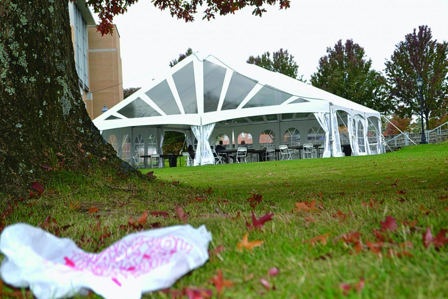 A plastic bag from the Metz Dining Hall lies on the ground near the outdoor tent eating area as teachers and students are eating their take-out food.