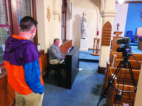 Senior Sean Gorman (left) assisting with filming of the Alumni Memorial Mass for Homecoming Weekend. Raymond Podskoch '90 on piano playing hymns.