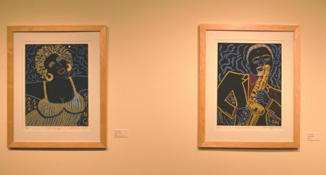 """Mama Can Sing"" (left) and ""Papa Can Blow"" (right) by Faith Ringgold hang in the art gallery. One of the key features of these pieces is the gold leaf Ringgold uses, which can be seen more clearly with a magnifying sheet."
