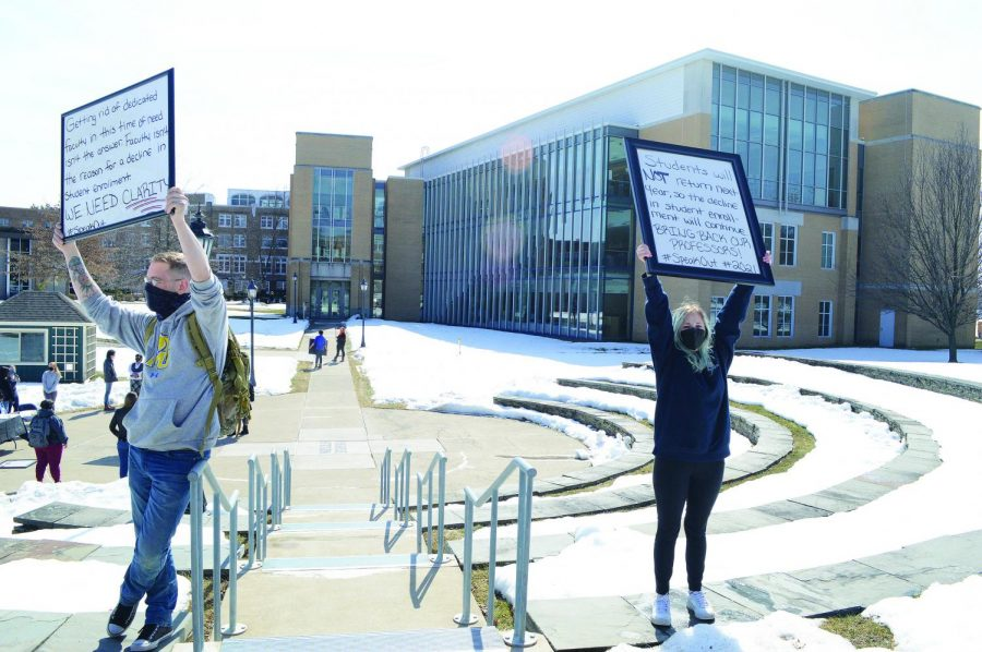 Tyler Meyers (left) and Emily Martin (right) hold up signs at a peaceful demonstration.