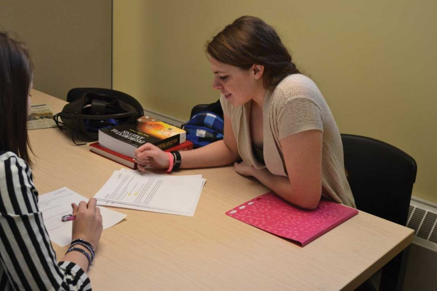 Amelia Poplawski looks through notes to answer a question during a tutoring session in the Tutoring Center Hall.