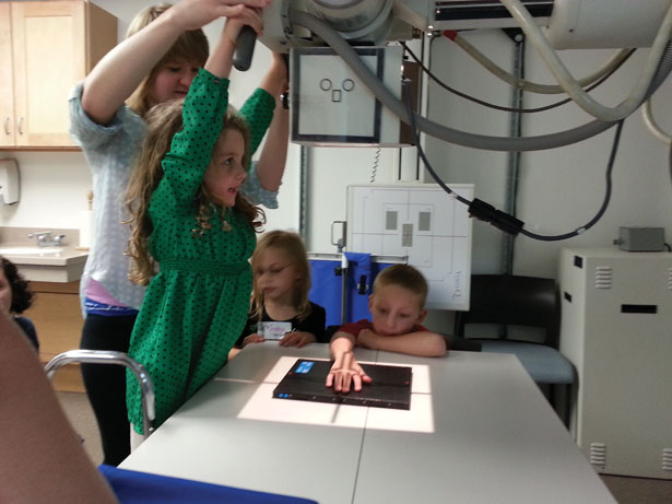 Donya Forst helps her bone buddy Amelia take an x-ray of another bone buddy's hand in the energized lab in Mercy Hall.