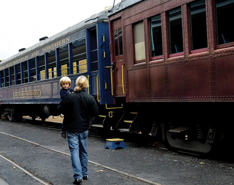 A young boy and his father get ready to board the Autumn Breeze train car.