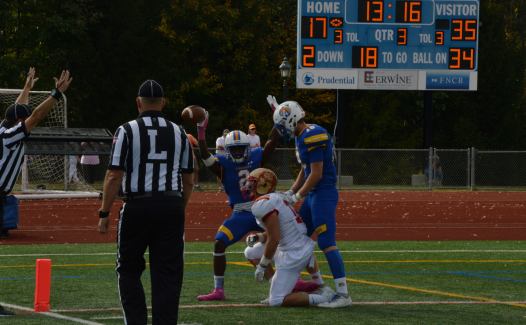 Quarterback Tom Madeo, #18, and wide-receiver Isaiah Williams, #2, pose as they score a touchdown against King's.