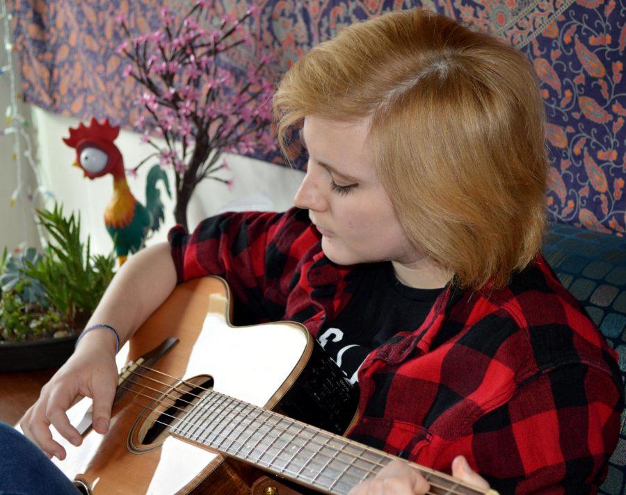 Becca Cristino strums her guitar.