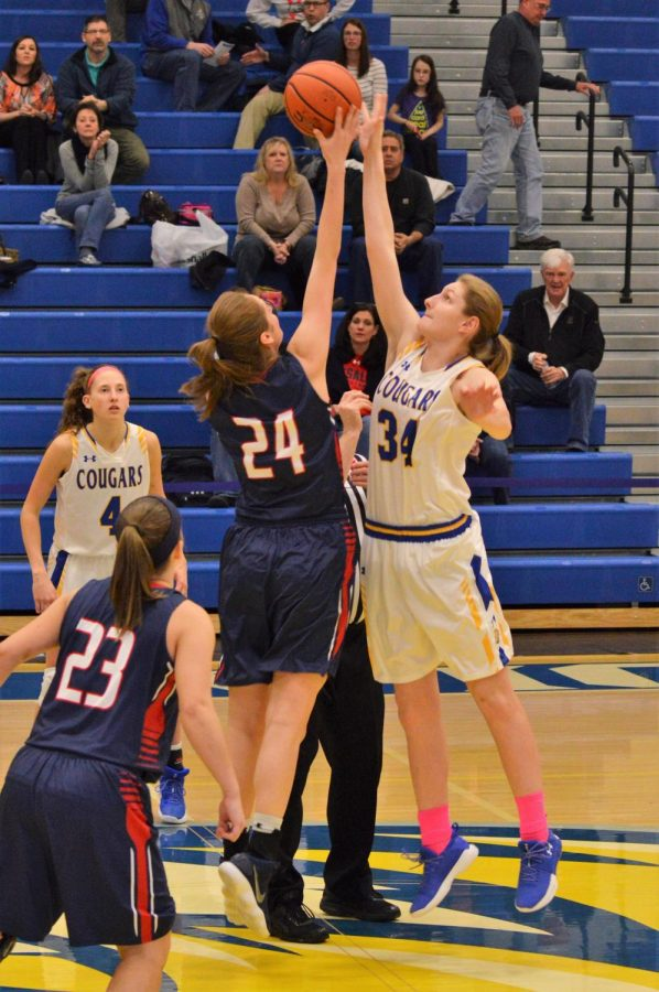 Misericordia's #34,  sophomore. Paige Wampole serves up against DeSales' #24, sophomore, Molly Jansco.