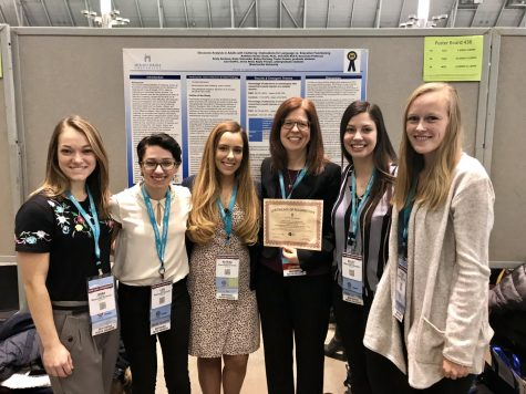 From left to right, Jenna Reed, Lisa Giuffre, Katrina Giacumbo, Dr. Kathleen Scaler Scott, Bailey Hartung, and Taylor Header pose in front of their recognized poster.