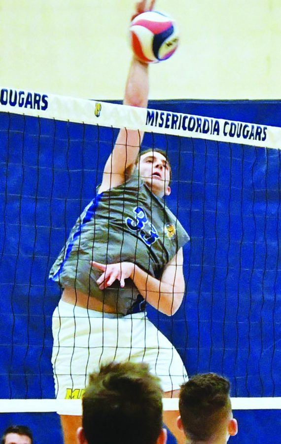 Brian Ross, senior outside hitter for the men's volleyball team, hits the ball over the net in an attempt to keep it away from the opposing team. Ross contributed 13 kills, 10 digs and one ace to the team's first match against Steven Institute of Technology on March 6, helping the Cougars earn a 3-1 win.