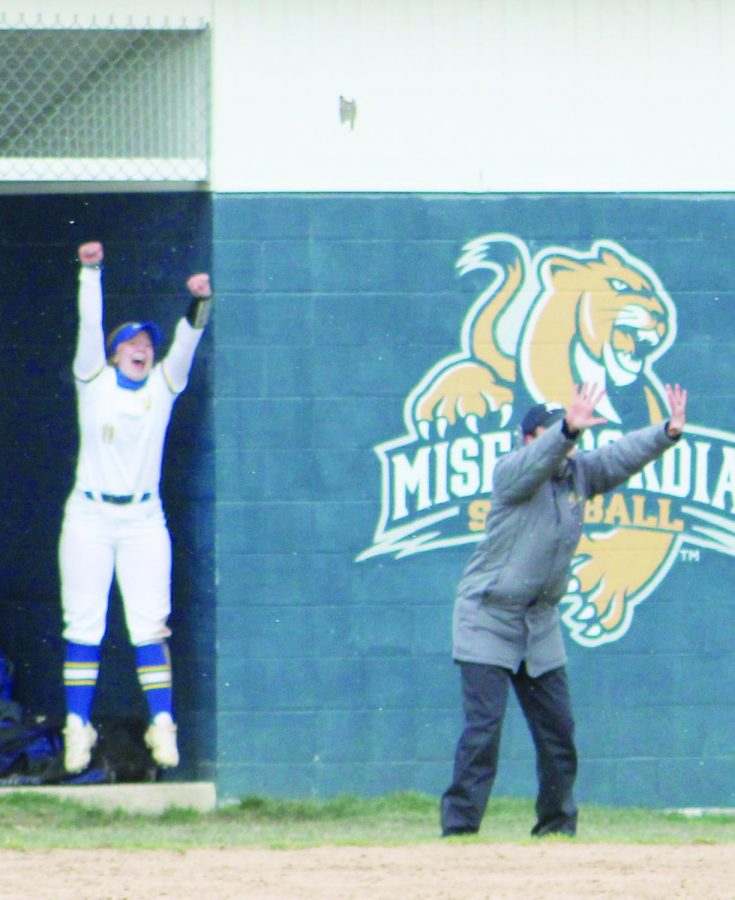 #11 Nicole Elliot, freshman second base shortstop and nursing major, and head coach Lindsay McCarthy cheer as the Cougars earn another point. The softball team maintained a solid record for the season.