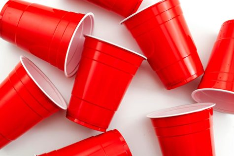 College party and beer pong concept with red drinking plastic cups on white background